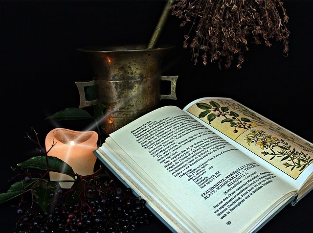 A home remedy recipe book, candle and herbs.