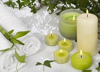Aromatherapy candles being lit next to towels