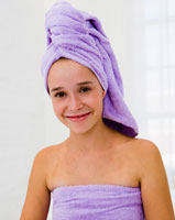 A young girl with her washed hair in a towel.