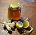 a jar of organic honey, ginger and 2 lemon halves