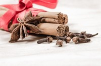 A bundle of cinnamon sticks tied together with a red ribbon with star anise and cloves.