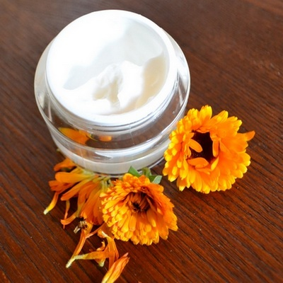 homemade face moisturize cream and calendula flowers on a wooden board.