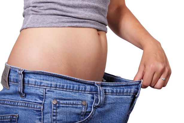 A young woman in a pair of jeans showing weight loss